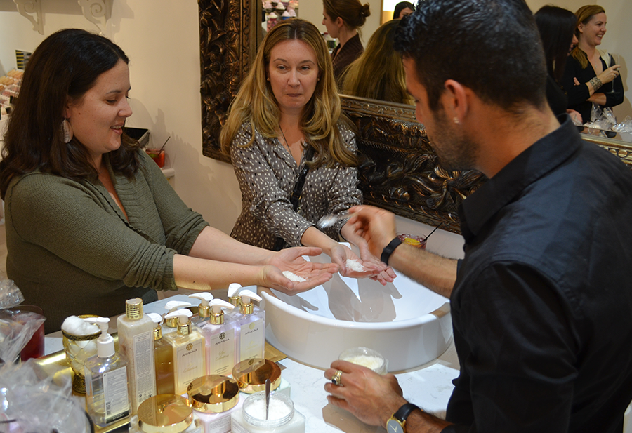 Arianna' skin specialist demonstrates the Ultra Exfoliating Body Treatment in the hands of two customers.