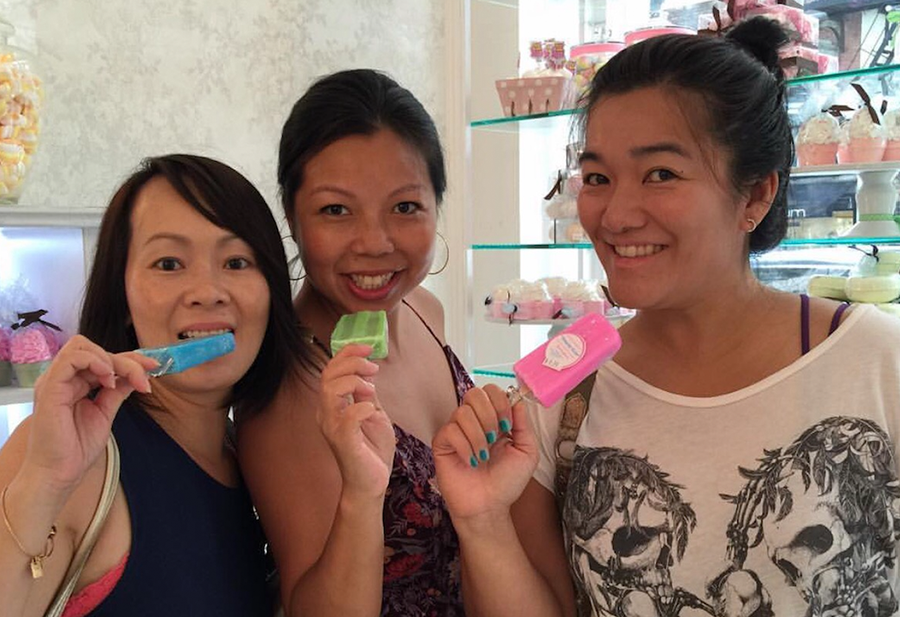 Three women pretend to eat a lollipop-shaped soap in the colors blue, green and pink.