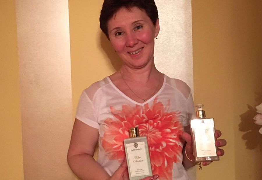 A woman smiles to the camera holding one product from Arianna Elite Collection in each hand.