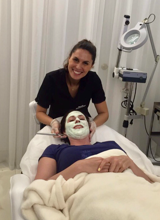 Skincare specialist Rachel poses while offering a facial treatment to a customer that is laying down with a green mask in her face.