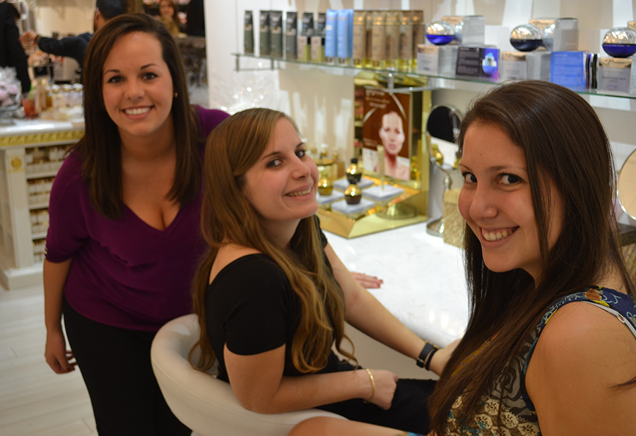 Three young women are sitting and smiling while waiting for their skin demonstrations.