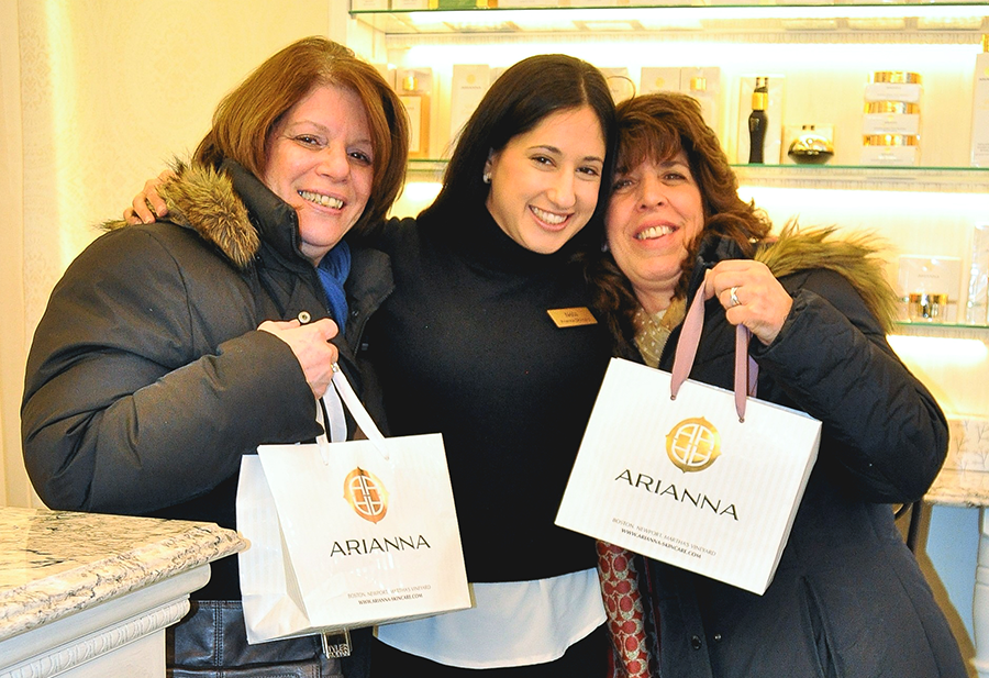 Two customers hug Arianna's saleswoman while smiling and showing their shopping bags.