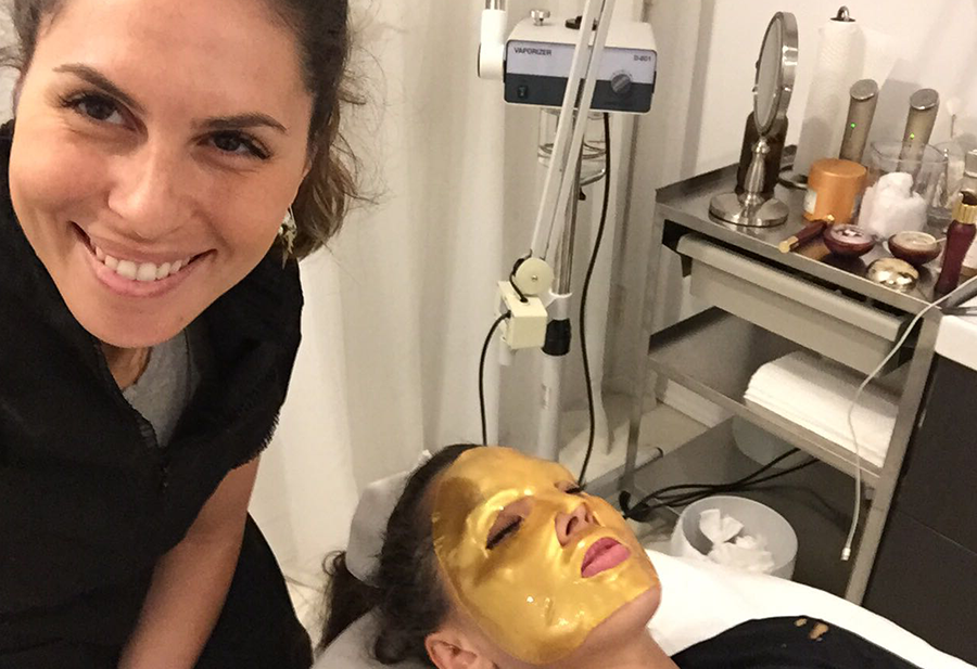 Skin specialist takes a selfie with a customer receiving a gold mask treatment.