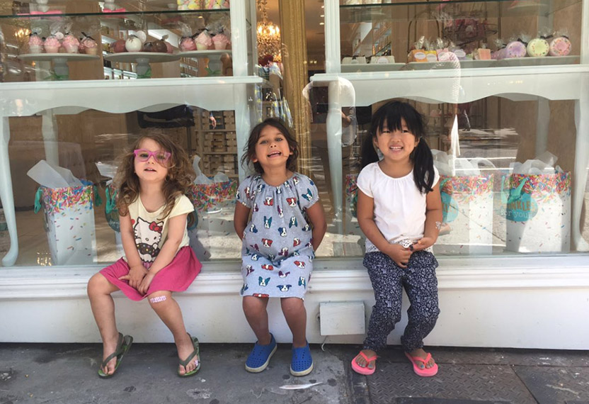 Three girls are sitting in front of Arianna' store, smiling to the camera while waiting for their mothers.