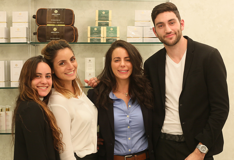 Arianna's founder and her team pose to a photo in front of the products. They are smiling and hugging.