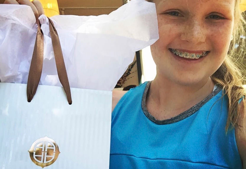 A young blond girl with braces smiles to the camera holding an Arianna Skincare shopping bag.