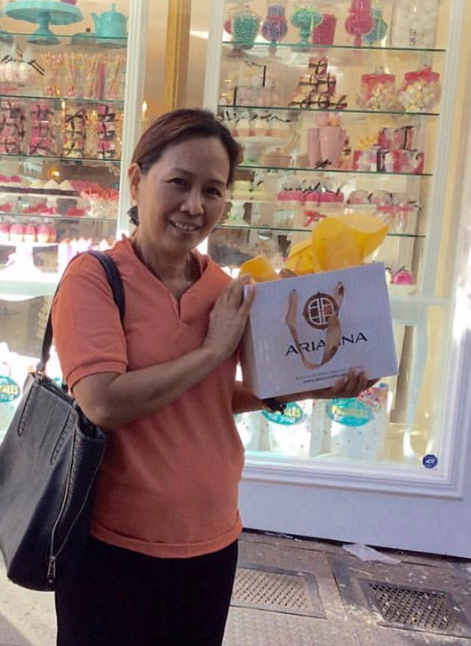 A woman poses with her purchase in front of Arianna store. In the background appears all candy-shaped products from the Indulgence Collection.