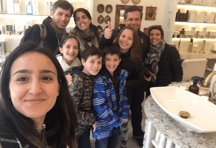 A big family of tourists takes a selfie inside Arianna' store.
