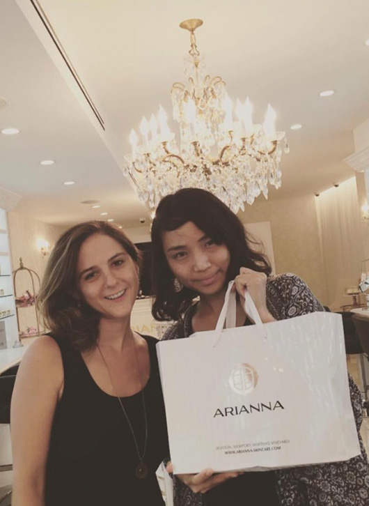 Two young women hold a big shopping bag from Arianna under the crystal chandelier at Soho store.