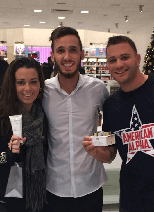 Three customers, two men and a woman, pose for a picture holding Arianna Skincare's products.