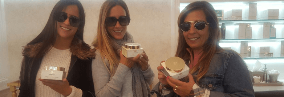 Three beautiful women with sunglasses hold Arianna's body butter jars.