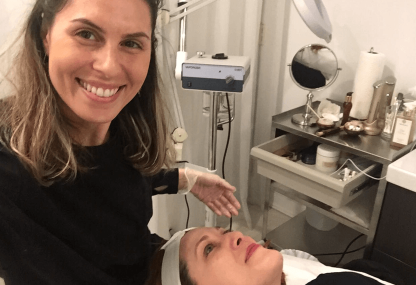 A team member from Arianna Skincare smiles to the camera while giving a facial treatment to a customer.
