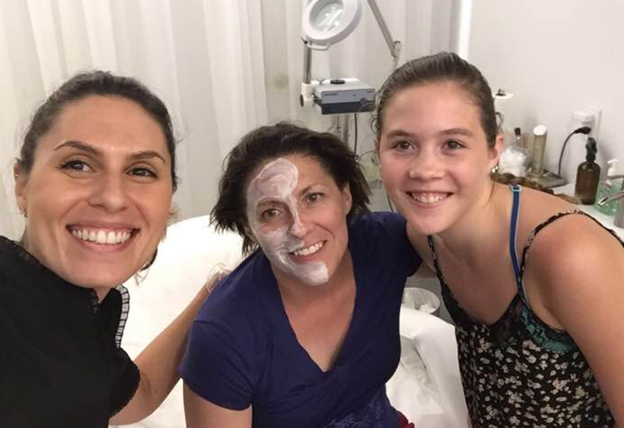 A woman receiving a facial treatment in the right side of her face (to compare the immediate results) poses for a picture with her daughter and the skin care specialist.