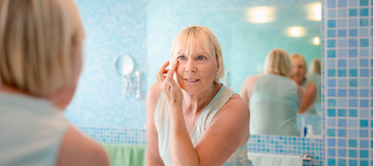 senior woman applying lotion on the face in a bathroom at home