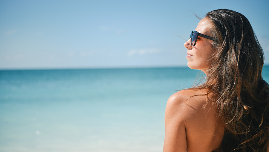 a young woman at the beach with sunglasses, looking at the horizon
