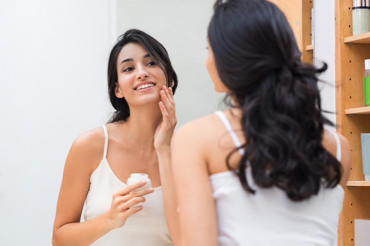 young woman applying facial moisturizer