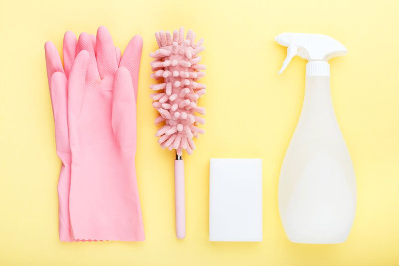 concept cleaning, on a yellow background pink gloves, a soft dust brush, melamine sponge and spray for glasses