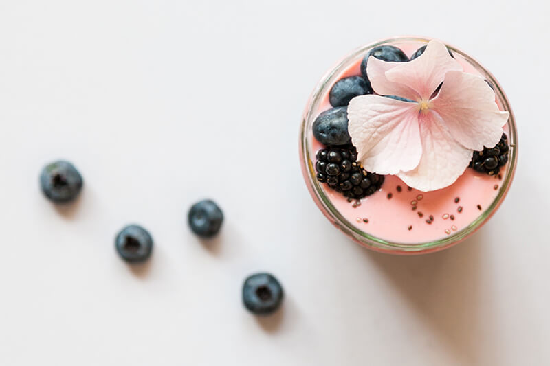 smoothie with black and blueberries and a decorative pink flower