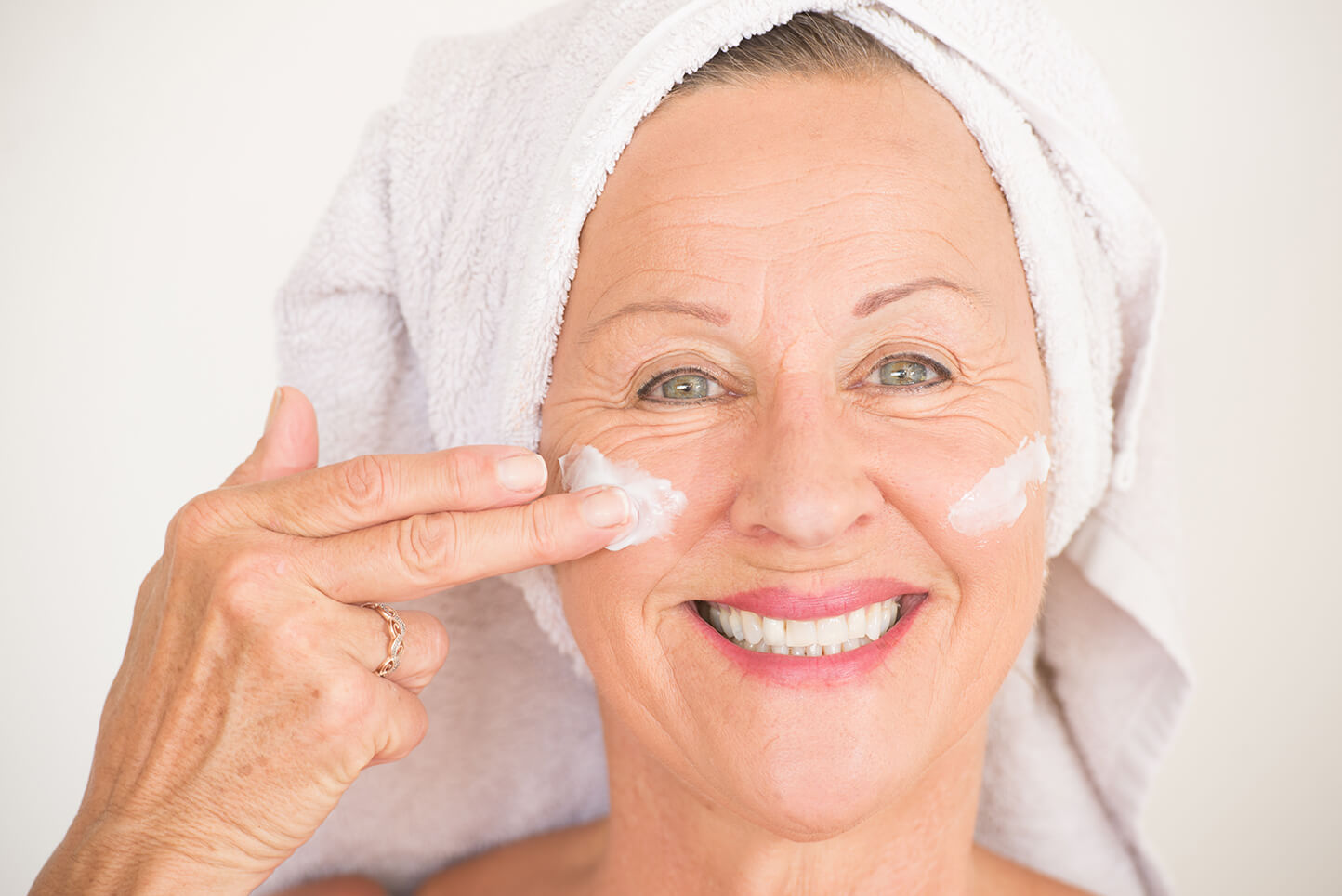 Portrait friendly attractive mature woman with towel and moisturizer lotion on happy smiling face, bright background.