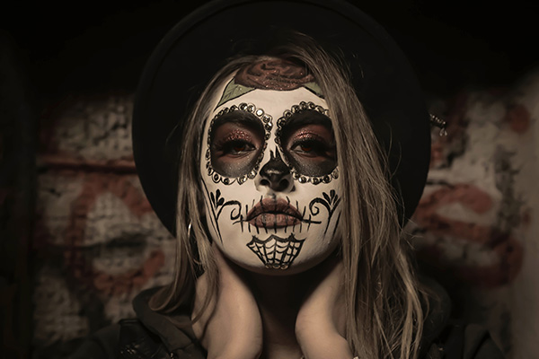 young woman wearing a Halloween mask
