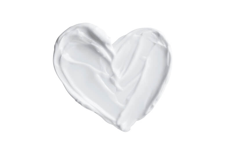Heart shaped from skincare cream on white background. Valentine's day creative concept.